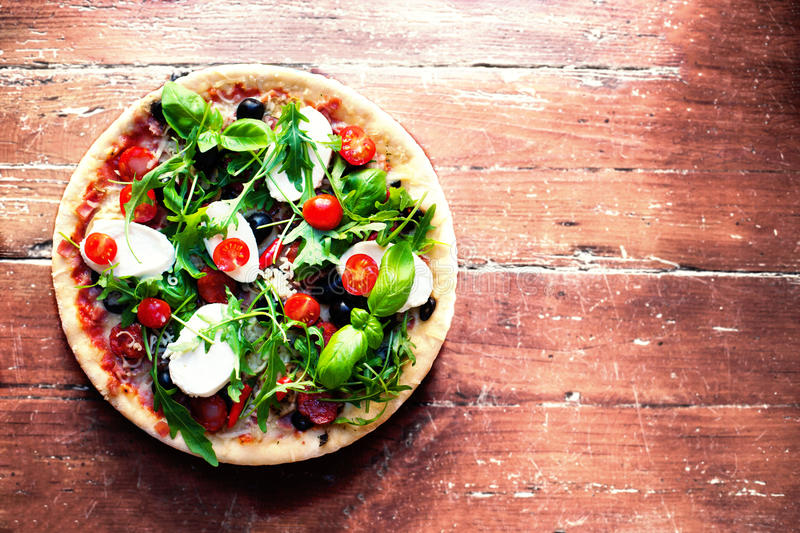 Hot pizza with meat, basil and mozarella cheese on a dark background, top view. Pizza on the rustic wooden table with copy space. royalty free stock photography