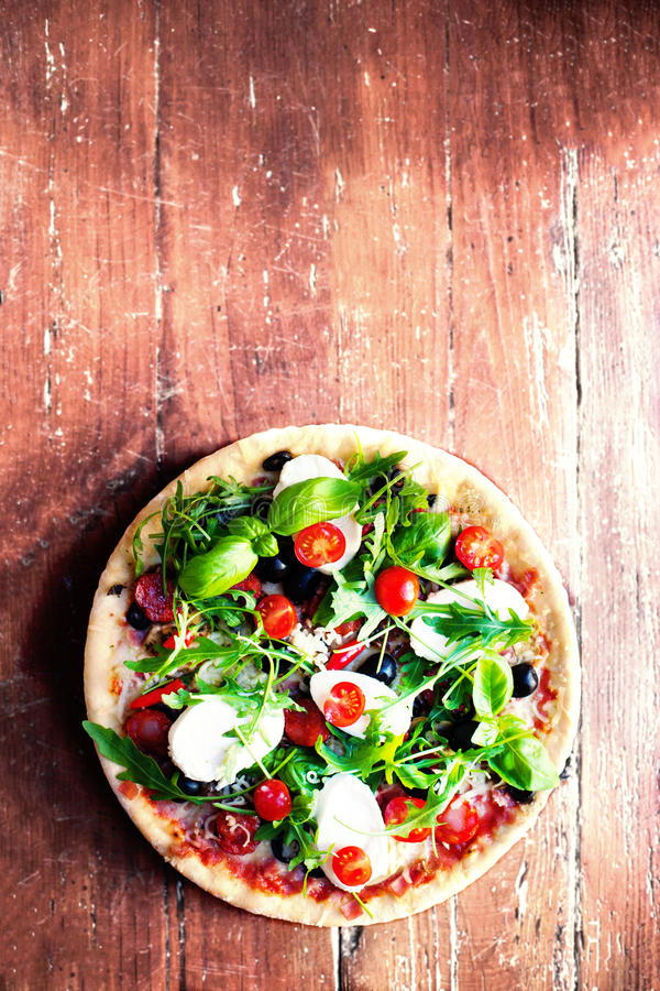 Hot pizza with meat, basil and mozarella cheese on a dark background, top view. Pizza on the rustic wooden table with copy space. royalty free stock photo