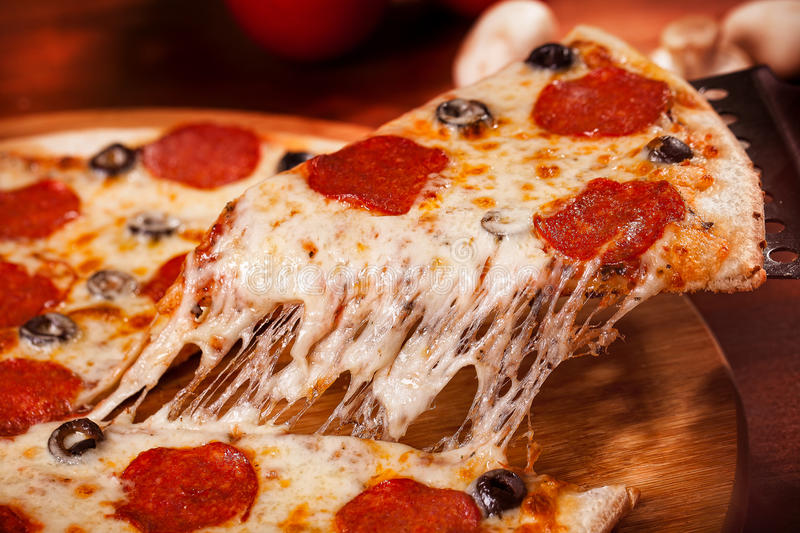 Hot Pizza. A slice of Hot Pizza on the wooden table stock photos