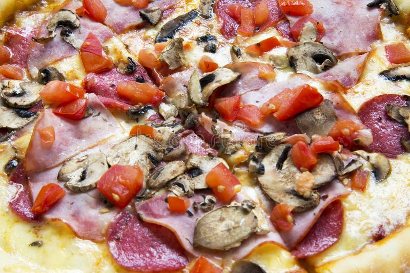 Hot pizza with tomatoes, bacon, salami, cheese and mushrooms, closeup. stock photo