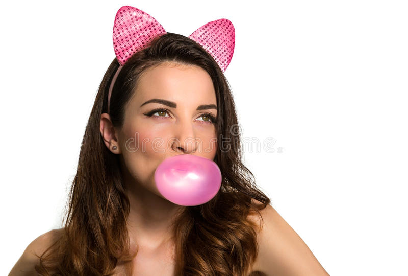 Pretty woman blowing a bubble with gum. Pretty young brunette woman with pink ears blowing a bubble with chewing gum, white background royalty free stock image