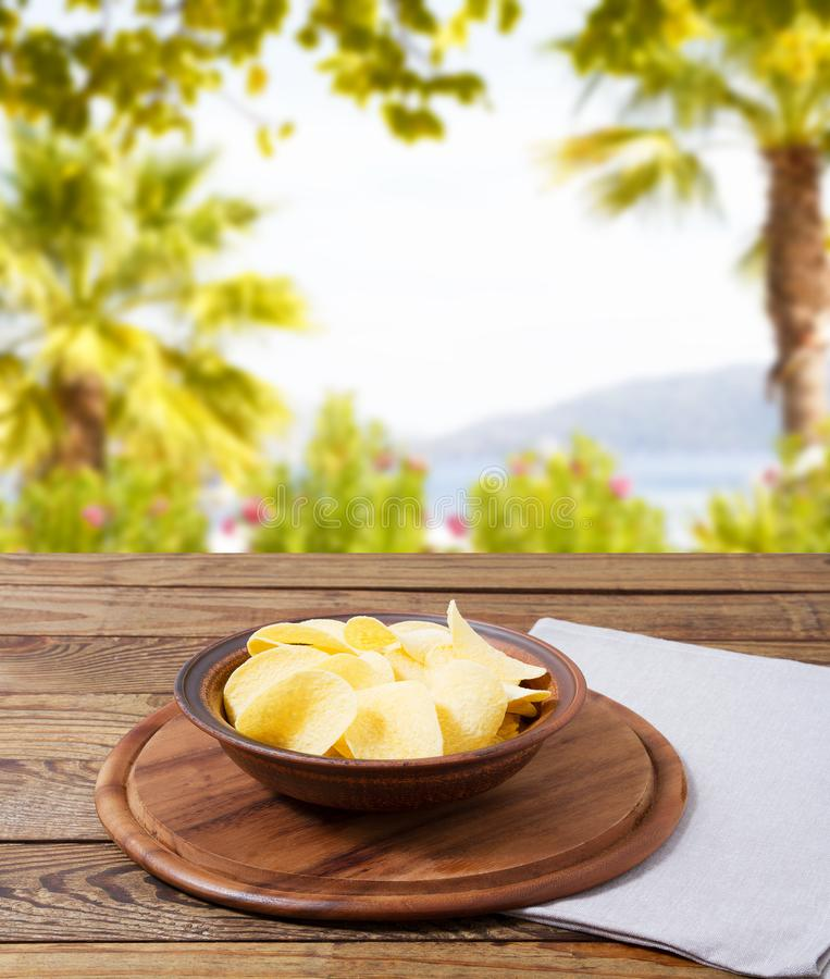 Hot potato chips, grow napkin wooden table on blurred sunshine park background,mock up,copy space.  royalty free stock photo