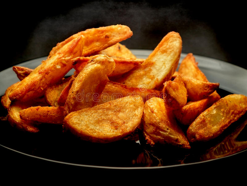 Hot potato wedges on black plate stock image