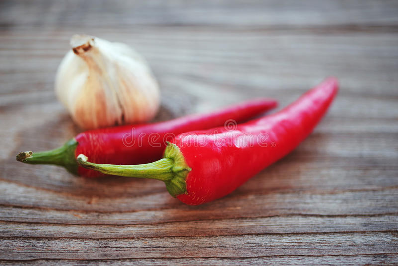 Hot red chili pepper and garlic. On a wooden background, soft focus royalty free stock image