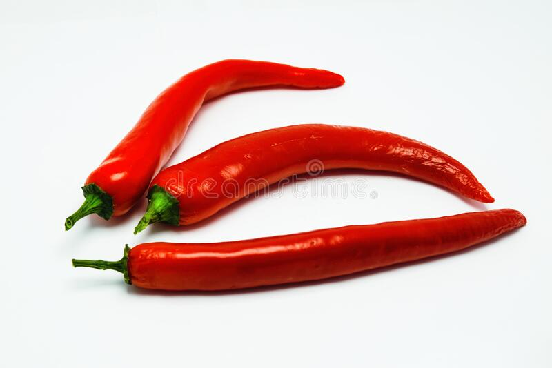 Hot red chili peppers close-up isolate on a white background. Red chili peppers isolated against a white background stock photography