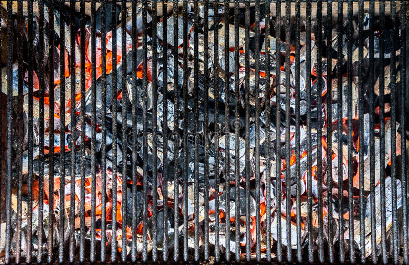 Hot red coal under barbecue grill. Charcoal is ready for grilling stock image