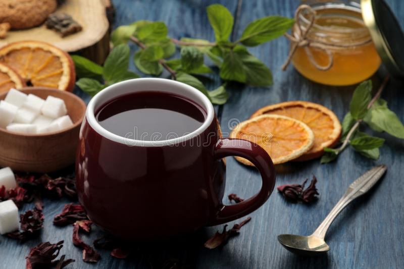 Hot red karkade tea with honey and mint. Autumn or winter soft drink. on blue wooden table royalty free stock photography