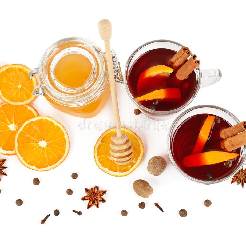 A Hot red mulled wine, bee honey, slices of oranges and spices isolated on white background. Flat lay, top view stock images