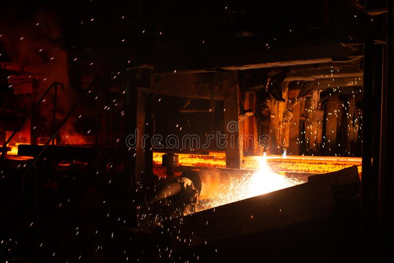 Hot red steel billets at torch cutting. Background of the blacksmith and metallurgical industry. Steel factory stock photography