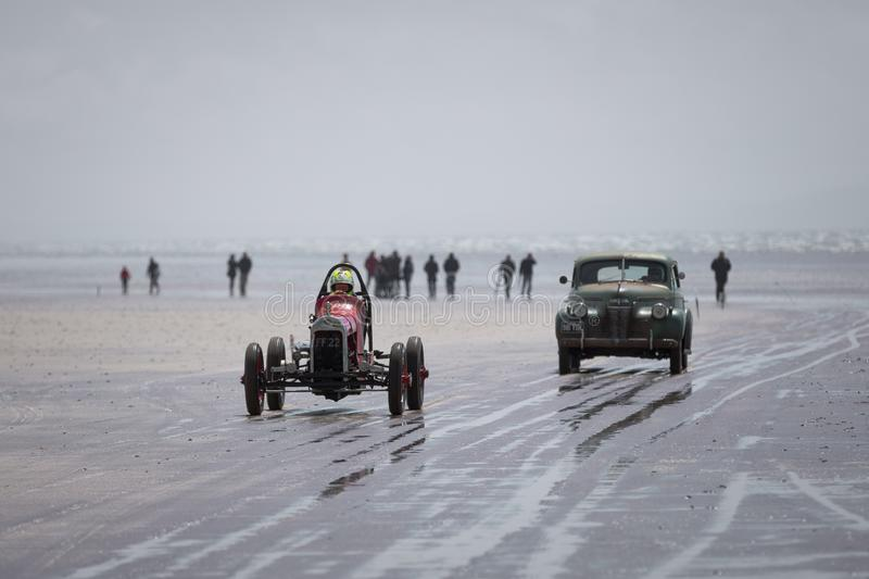 Hot Rod Races - Two Hot Rods driving up the beach with crowds in the background. Pendine Sands, Carmarthenshire / Wales - June 16th 2019 : Hot Rod Races - Two stock photos