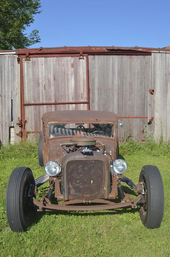 Hot rod roadster. An old rusty hot rod roadster is parked in front of a weathered box car royalty free stock photos
