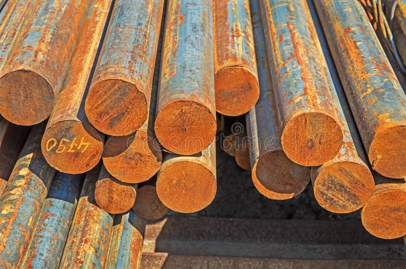 Hot-rolled round steel bars. The rusty hot-rolled round steel bars in packs at the warehouse of metal products piled in the open air stock photo