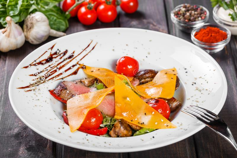 Hot salad with beef steak chargrilled to medium rare with cherry tomatoes, mushrooms and cheese on dark wooden background. Hot Meat Dishes. Ingredients on royalty free stock images