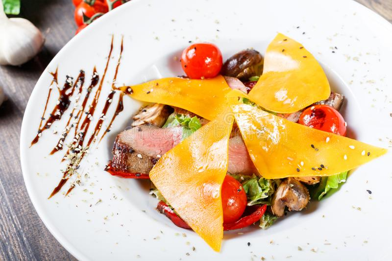 Hot salad with beef steak chargrilled to medium rare with cherry tomatoes, mushrooms and cheese on dark wooden background. Hot Meat Dishes. Ingredients on stock photo