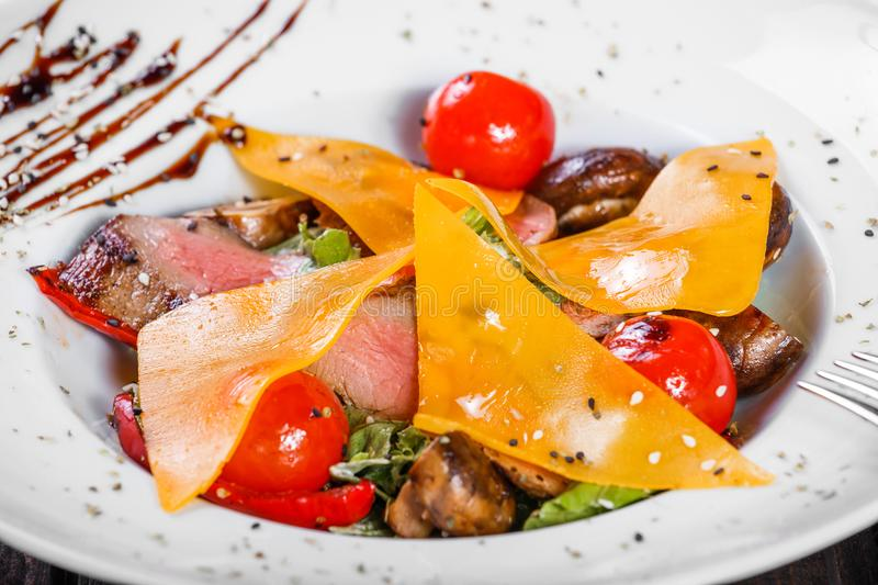 Hot salad with beef steak chargrilled to medium rare with cherry tomatoes, mushrooms and cheese on dark wooden background. Hot Meat Dishes. Ingredients on stock photography