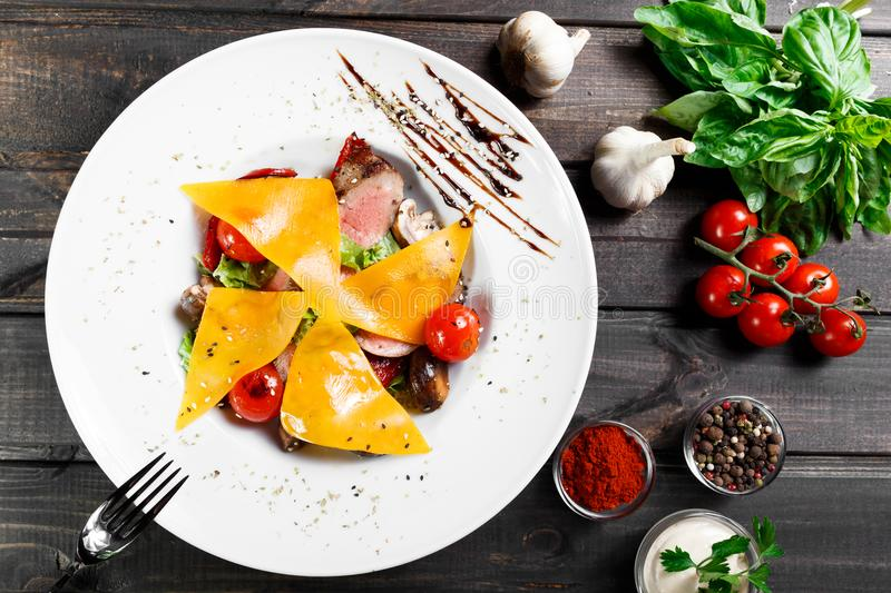 Hot salad with beef steak chargrilled to medium rare with cherry tomatoes, mushrooms and cheese on dark wooden background. Hot Meat Dishes. Ingredients on royalty free stock photos