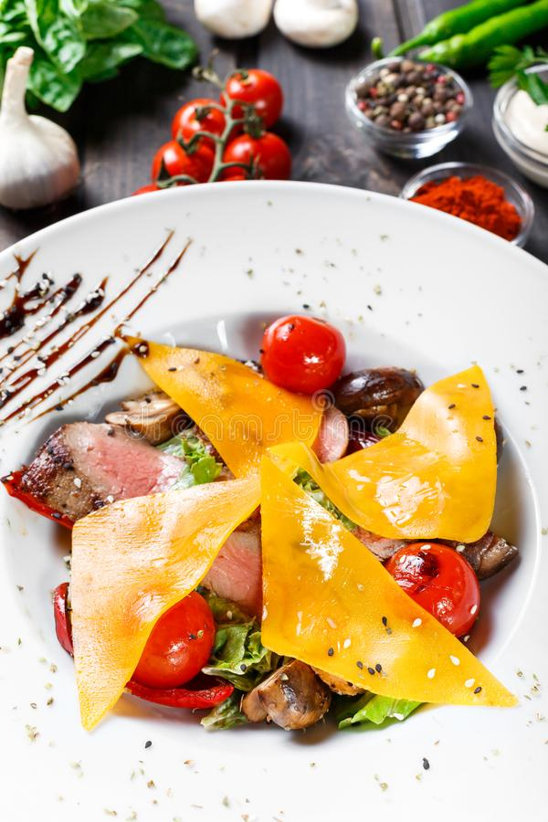 Hot salad with beef steak chargrilled to medium rare with cherry tomatoes, mushrooms and cheese on dark wooden background. Hot Meat Dishes. Ingredients on royalty free stock photo