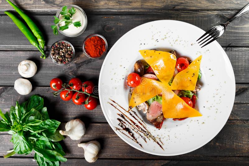 Hot salad with beef steak chargrilled to medium rare with cherry tomatoes. Mushrooms and cheese on dark wooden background. Hot Meat Dishes. Ingredients on stock image