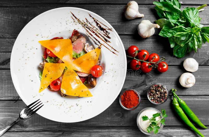 Hot salad with beef steak chargrilled to medium rare with cherry tomatoes, mushrooms and cheese on dark wooden background. Hot Meat Dishes. Ingredients on stock photos