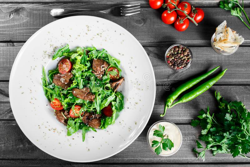 Hot salad with fried liver, cherry tomatoes and mixed greens on dark wooden background. Healthy food. Ingredients on table. Top view royalty free stock photography