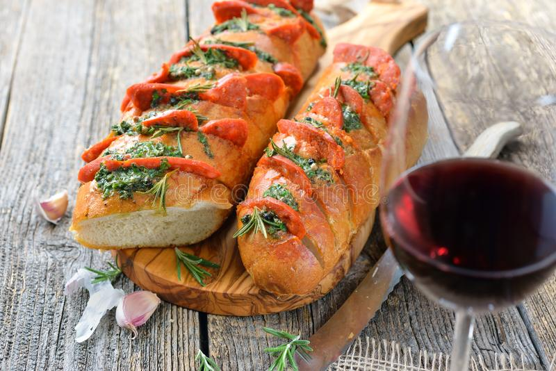 Hot salami baguette with wine. Spanish food: Roasted bread with herb butter and hot Chorizo salami fresh from the oven served with a glass of tempranillo red stock photography
