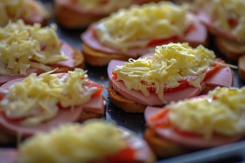 Hot sandwiches. Procurement for simple and quick meals: bread with ham, cheese and tomatoes royalty free stock photography