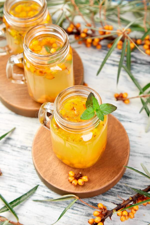 Hot sea buckthorn tea with ginger and honey. And sea buckthorn berries on white table. Top view. Vitaminic healthy royalty free stock image