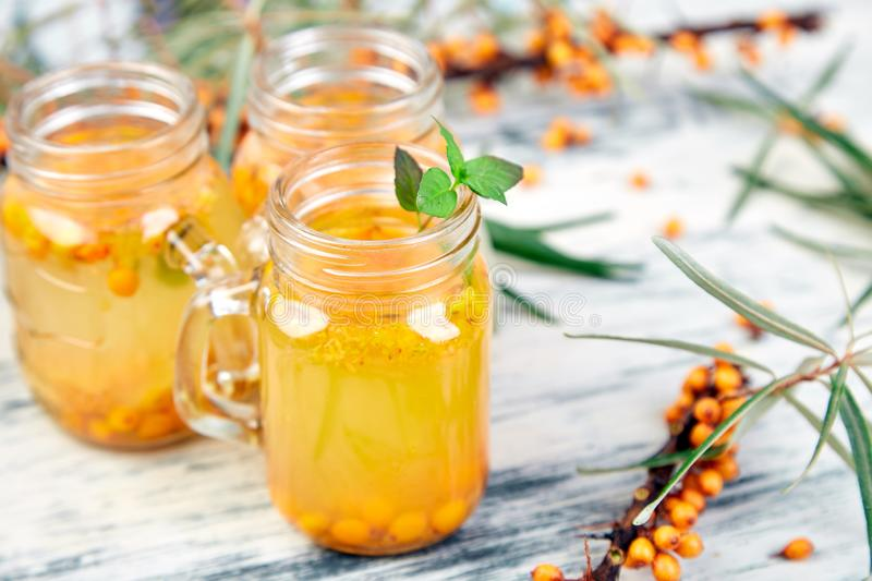 Hot sea buckthorn tea with ginger and honey. And sea buckthorn berries on white table. Top view. Vitaminic healthy royalty free stock photo
