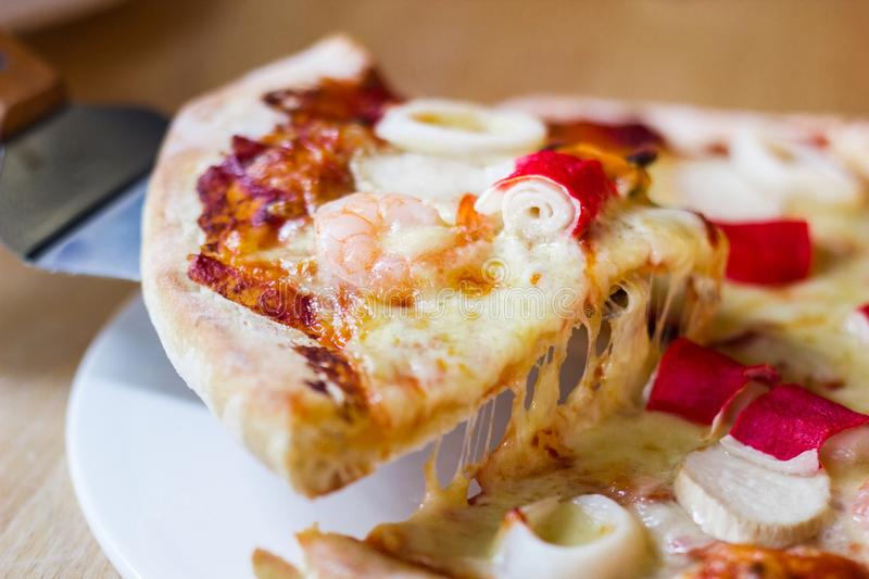 Hot seafood pizza slice with melting cheese on rustic wooden royalty free stock photos