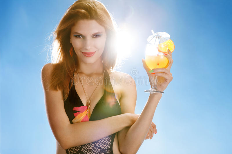 Hot season. Portrait of happy smiling girl wearing swimsuit with refreshing cocktail in her hand on blue background royalty free stock photos