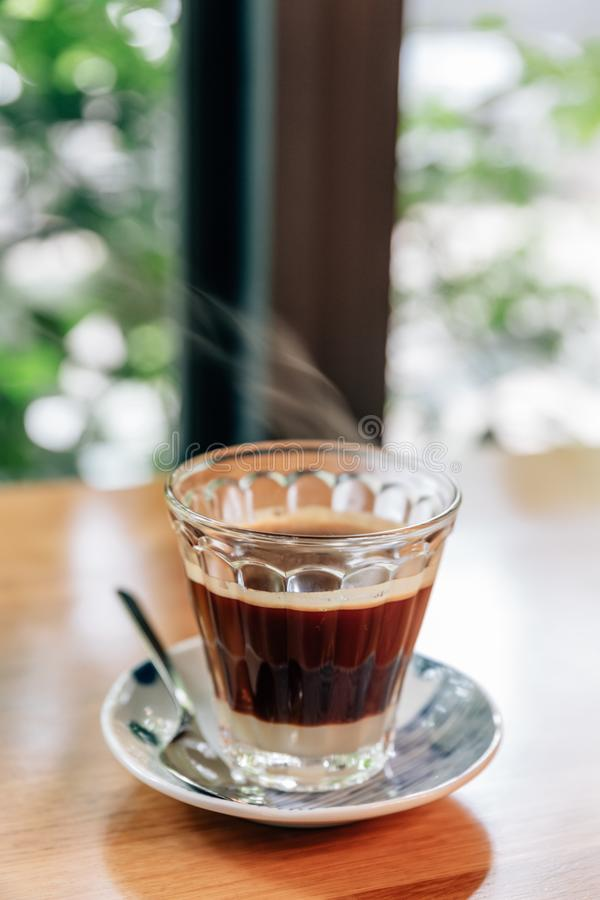 Hot served Vietnamese coffee that can wake you up: Black coffee mix with condense milk in clear glass served on wooden table. royalty free stock image