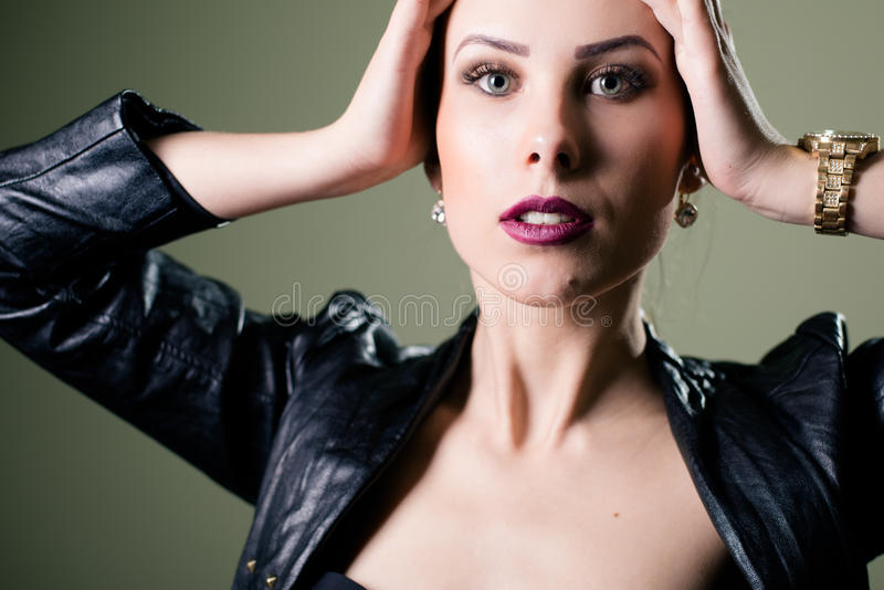 Hot pretty young lady wearing leather jacket. Close up portrait of hot pretty young lady wearing leather jacket sensually looking at camera on gray copy space royalty free stock images