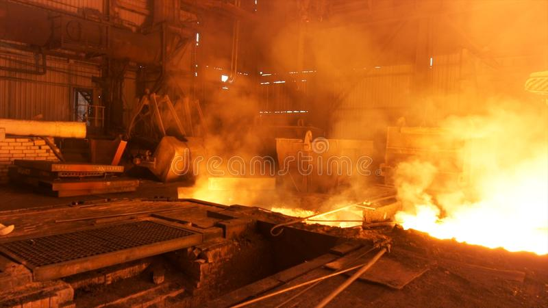 Hot shop at the metallurgical factory with molten steel in the chute. Stock footage. Metallurgical works, industrial. Hot shop at the metallurgical factory with stock image