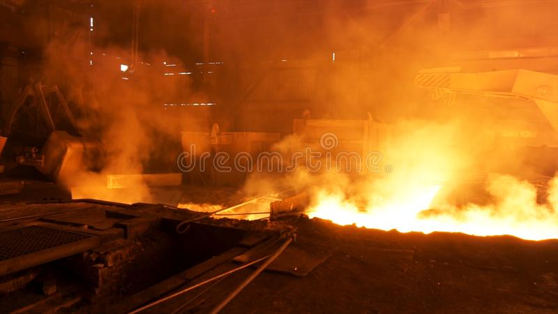 Hot shop at the metallurgical factory with molten steel in the chute. Stock footage. Metallurgical works, industrial. Hot shop at the metallurgical factory with stock images