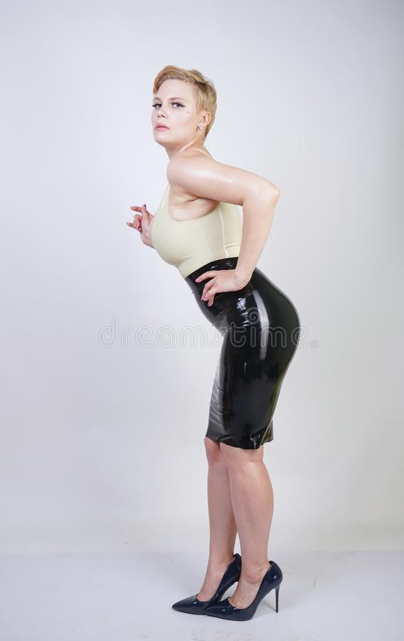 Hot short hair blonde girl with curvy body wearing latex rubber dress on white studio background royalty free stock photos