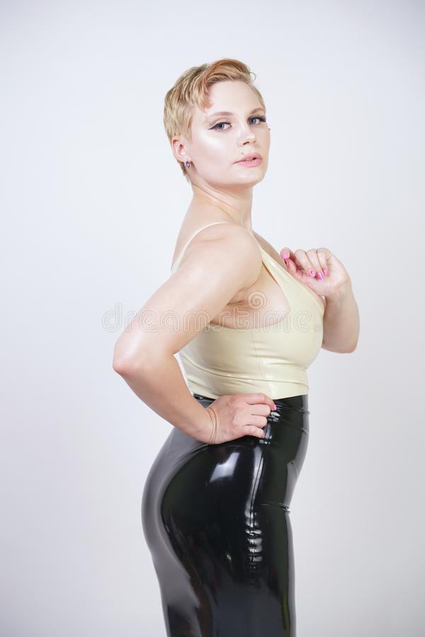Hot short hair blonde girl with curvy body wearing latex rubber dress on white studio background royalty free stock images