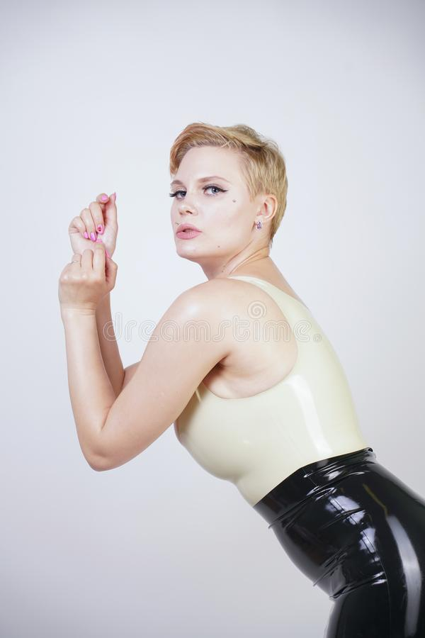 Hot short hair blonde girl with curvy body wearing latex rubber dress on white studio background royalty free stock photography