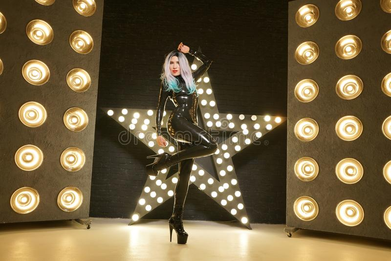Hot slim woman posing in latex rubber fashion clothes on black background with yellow lights bulbs royalty free stock photo