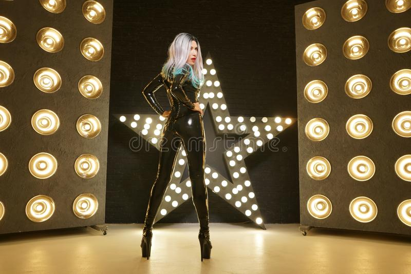 Hot slim woman posing in latex rubber fashion clothes on black background with yellow lights bulbs stock images