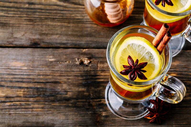 Hot spiced Apple cider Toddy with lemon, honey and cinnamon stick in glass stock photography