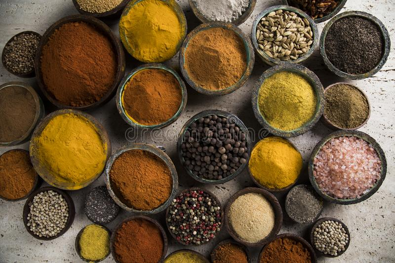 Hot spices in wooden bowls. Variety of spices and herbs on kitchen table royalty free stock images