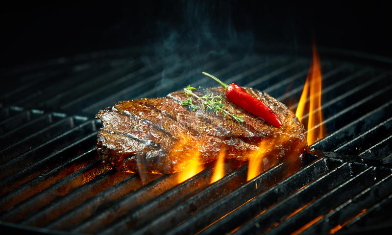 Hot spicy chili steak grilling on a barbecue. Hot spicy chili steak grilling on a summer barbecue over the flaming hot coals garnished with a whole red cayenne royalty free stock images