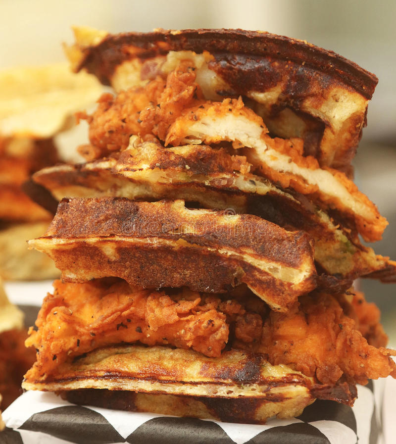 Hot spicy fried chicken cutlet on grilled Belgian waffles. Triple decker spicy hot fried chicken waffle sandwich royalty free stock photo