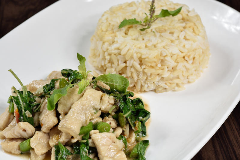 Hot and spicy fried pork with Thai Organic Brown Rice. stock photo