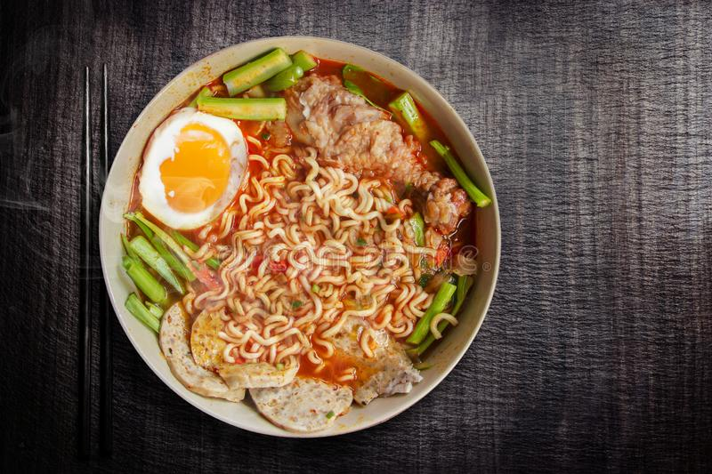 Hot and Spicy noodle in bowl and ingredients on wood background, Korea noodles with boil eggs, copy space and top view. Hot and Spicy noodle in bowl and royalty free stock photos