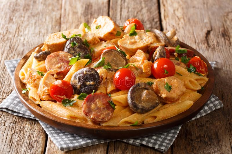 Hot spicy penne pasta with fried chicken, wild mushrooms, smoked sausage, tomatoes and creamy cheese sauce close-up on a plate on. The table. horizontal stock photos