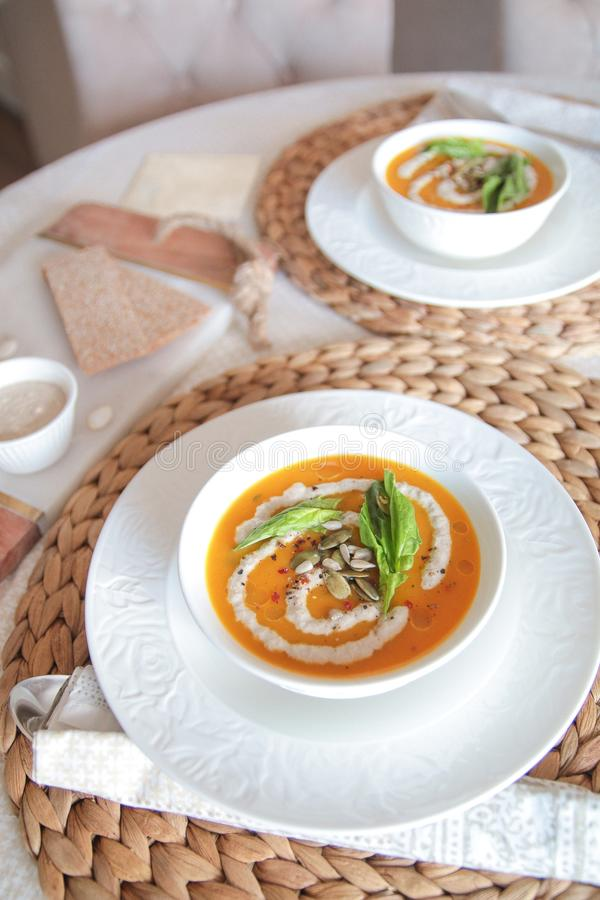 Vegetarian pumpkin puree soup with sunflower cream royalty free stock photography