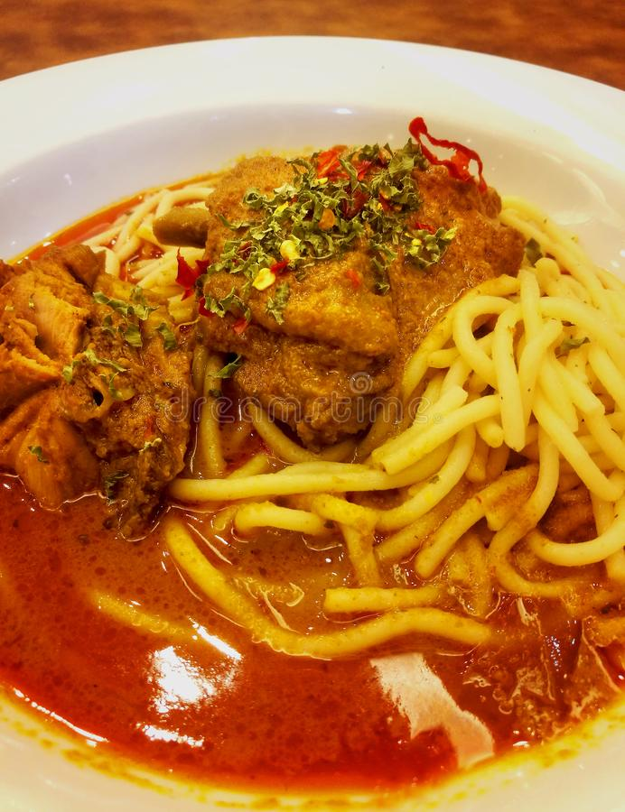 Hot and spicy rendang chicken noodle on the table. Rendang chicken is one of the most famous dishes in the Malaysia cuisine stock images