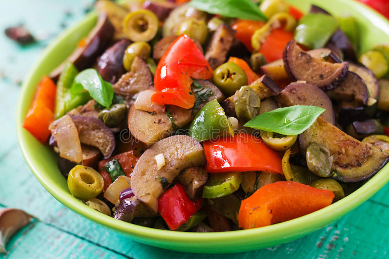 Hot spicy stew eggplant, sweet pepper, olives and capers. stock photos