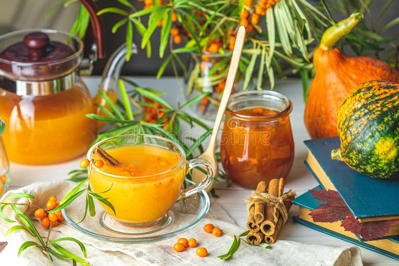 Hot spicy tea with sea buckthorn in glass cup and teapot, selective focus, rustic light background. Cup and teapot of hot spicy tea with sea buckthorn, jam in stock photography